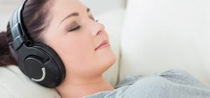 hypnosis downloads - girl with eyes closed wearing headphones