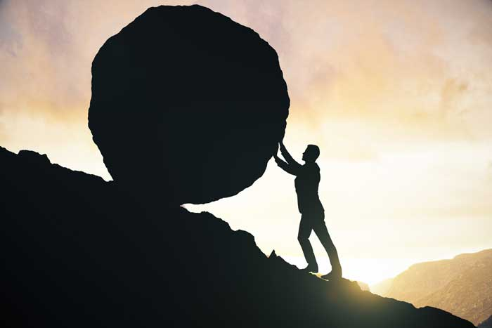 man pushing boulder up hill to represent overcoming problems with hypnotherapy and mind coaching