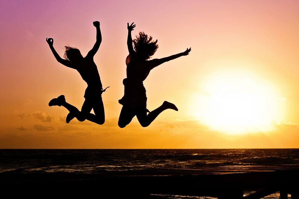 two girls jumping in the air in sunset sky