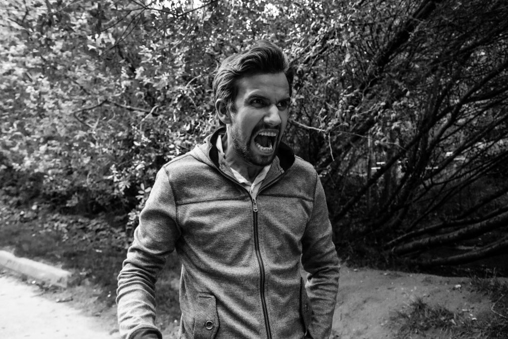 angry man running along the road