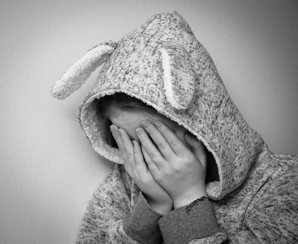 young girl in bunny costume hiding face