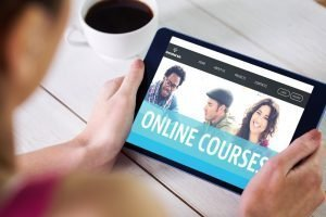 person holding ipad showing online courses