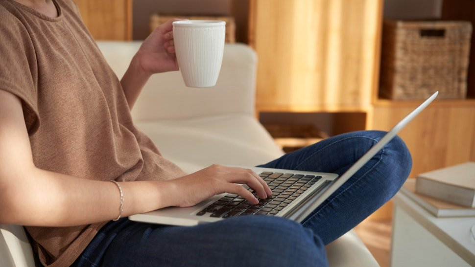 woman with cup of tea sitting at laptop getting ready for online therapy sessions