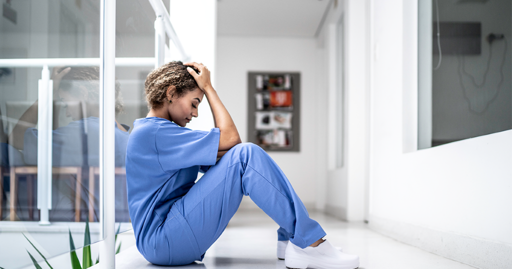 nurse sitting on floor suffering burnout