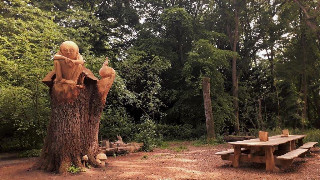 carved Buddha sitting in an old oak tree  at Thornham Walks, Suffolk