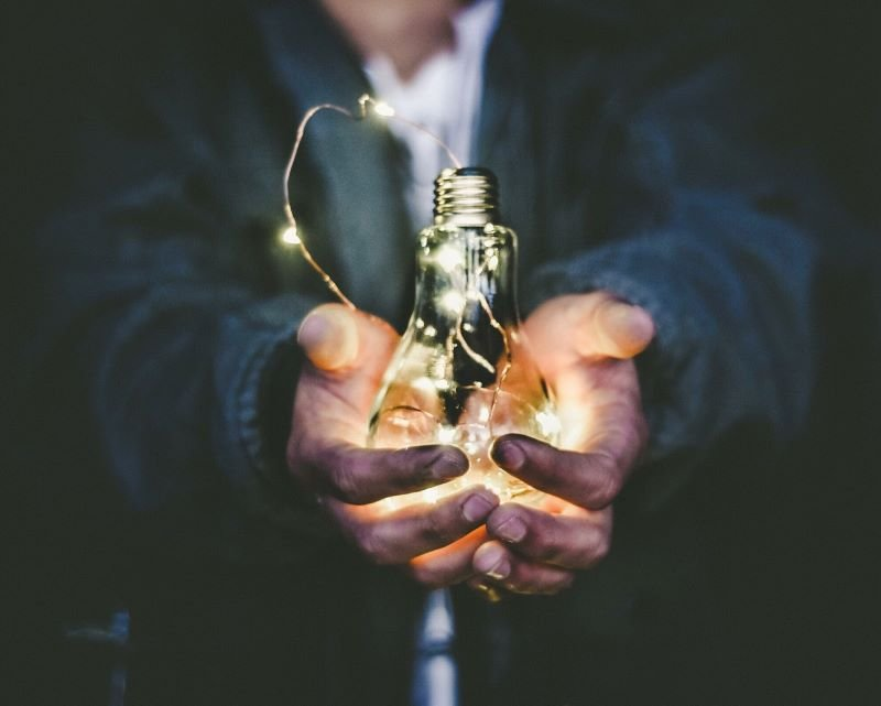 hypnotherapy supervision - man holding light bulb in hands